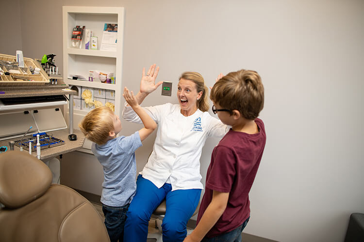 Doctor Tracy giving a high five to a little boy wearing a blue polo and a boy on their side