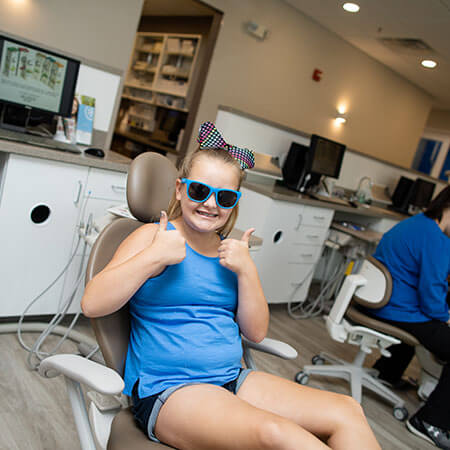 A little girl sitting in a dental chair wearing a blue top and sunglasses smiling and showing two thumbs up