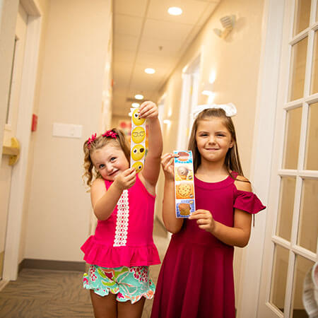 Two little girls standing in a hallway holding a sticker and smiling together