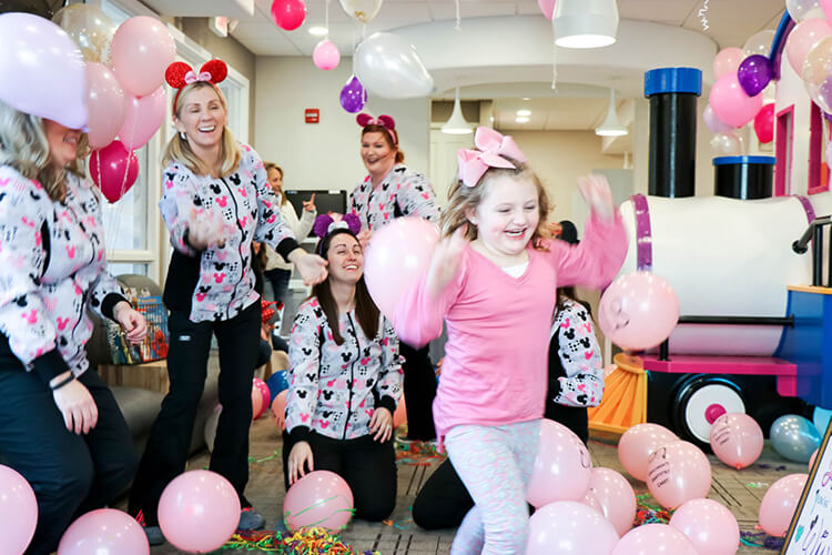 Team member wearing a minnie mouse themed headband and jackets playing with the little girl wearing a pink bow and top