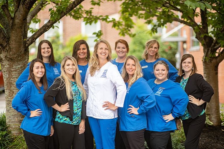 Doctor Tracy with team members smiling together with one hand on the hips wearing their dental uniform