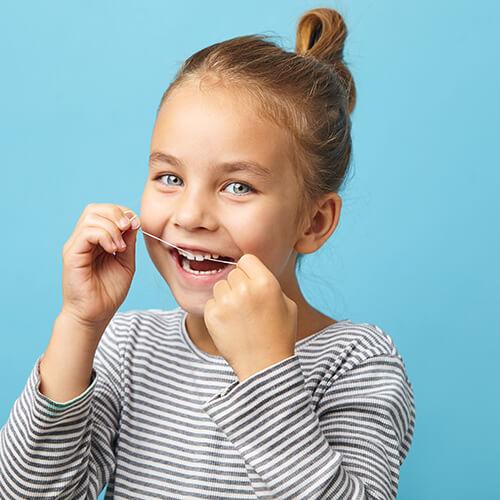 A little girl with brown hair wearing long sleeves flossing her teeth