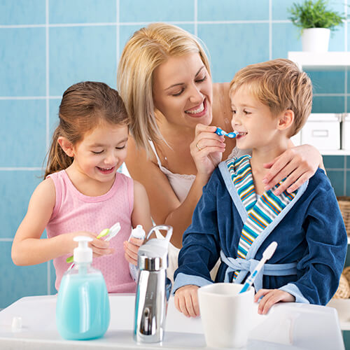A woman in a bathroom brushing the little boy's teeth and a little girl beside him holding a toothbrush and toothpast