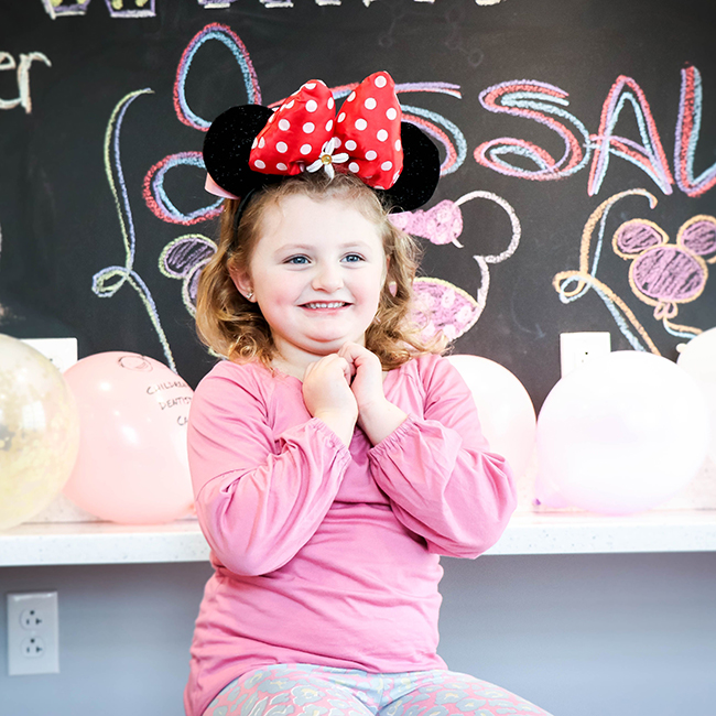 A little girl smiling and sitting wearing a Minnie mouse headband with her two hands in her chest